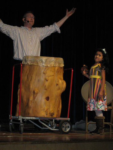 "Mark Shepard plays ""Bob, The Big Drum"" with the assistance of a young audience volunteer"