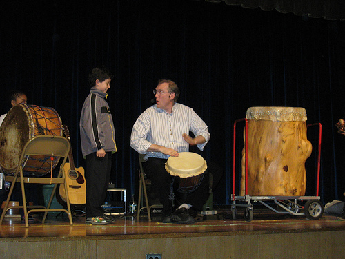 Mark Shepard shows a young audience volunteer what he'll be playing and the Djembe